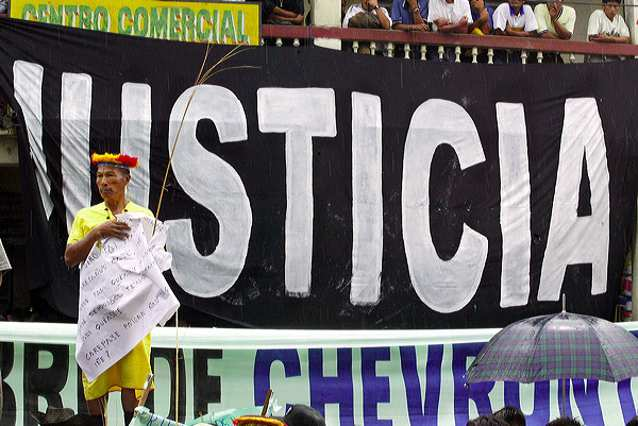 A Secoya elder stands in front of a banner reading Justice during a demonstration at the start of the trial against ChevronTexaco in Lago Agrio. Photo Credit: Lou Dematteis from Crude Reflections