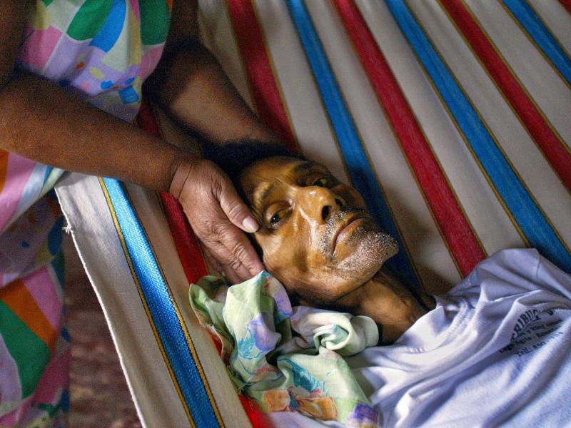 Luz Maria Marin holds the head of her husband Angel Toala the day before he died of stomach cancer in his home in Shushufindi. Photo Credit: Lou Dematteis, from Crude Reflections