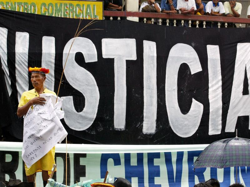 A Secoya elder stands in front of a banner reading 'Justice' during a demonstration at the start of the trial against Chevron in Lago Agrio, Ecuador. Photo Credit: Lou Dematteis, from Crude Reflections