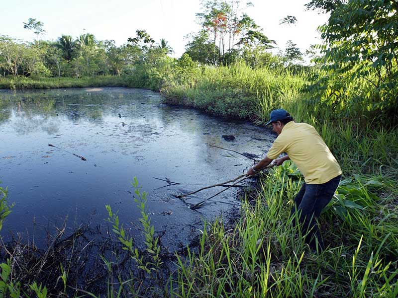 Donald Moncayo demonstrates an open oil waste pit left by Chevron in the Ecuadorian Amazon.